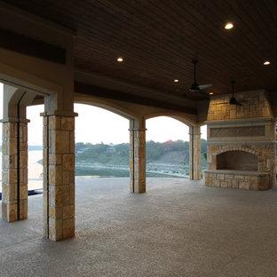Idéer för en stor medelhavsstil uteplats på baksidan av huset, med en öppen spis, granitkomposit och takförlängning