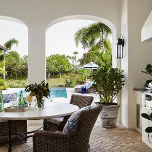 Ispirazione per un grande patio o portico tropicale dietro casa con pavimentazioni in mattoni e un tetto a sbalzo