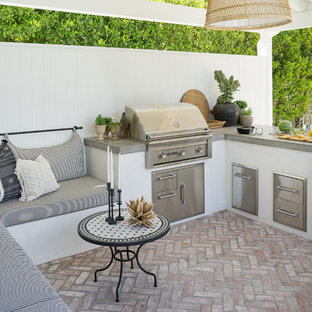 Inspiration for a coastal back patio in Orange County with an outdoor kitchen, brick paving and a gazebo.