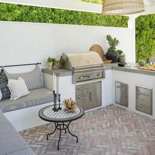На фото: беседка во дворе частного дома на заднем дворе в морском стиле с летней кухней и мощением клинкерной брусчаткой с