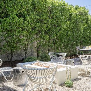 Ispirazione per un patio o portico costiero dietro casa con un focolare, ghiaia e nessuna copertura