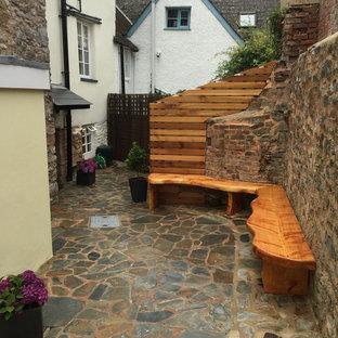 Idee per un piccolo patio o portico moderno in cortile con pavimentazioni in pietra naturale e nessuna copertura