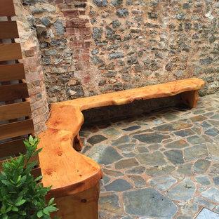 Idee per un piccolo patio o portico minimalista in cortile con pavimentazioni in pietra naturale e nessuna copertura