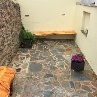Esempio di un piccolo patio o portico moderno in cortile con pavimentazioni in pietra naturale e nessuna copertura