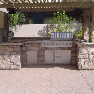 Example of a small classic backyard decomposed granite patio kitchen design in Phoenix with an awning