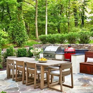 Ispirazione per un patio o portico chic di medie dimensioni e dietro casa con pavimentazioni in pietra naturale