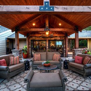 Foto di un patio o portico rustico di medie dimensioni e dietro casa con pavimentazioni in cemento e un tetto a sbalzo