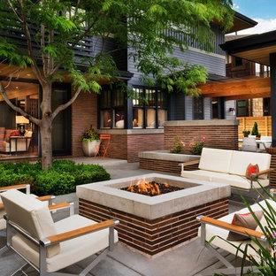 Idéer för en mellanstor modern uteplats på baksidan av huset, med en öppen spis och betongplatta