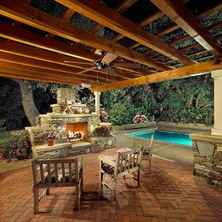 Ispirazione per un patio o portico boho chic di medie dimensioni e dietro casa con un focolare, pavimentazioni in mattoni e una pergola