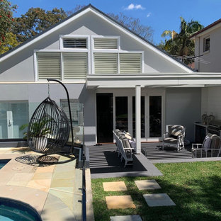 Example of a mid-sized cottage chic backyard stone patio kitchen design in Sydney with a pergola