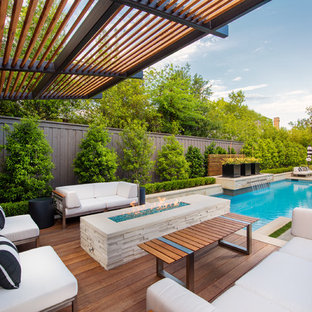 Cette photo montre une terrasse arrière chic de taille moyenne avec un foyer extérieur, une terrasse en bois et une pergola.