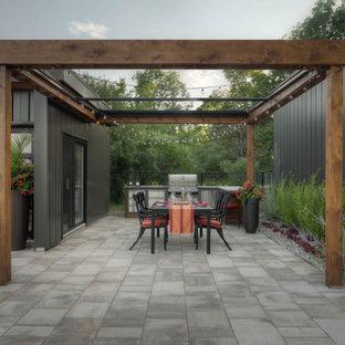 Imagen de patio minimalista, grande, en patio trasero, con cocina exterior, adoquines de piedra natural y pérgola