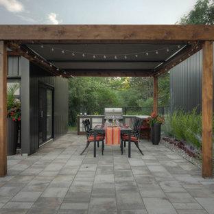 Ejemplo de patio minimalista, grande, en patio trasero, con cocina exterior, adoquines de piedra natural y toldo