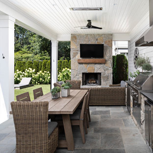 Esempio di un patio o portico country di medie dimensioni e dietro casa con pavimentazioni in pietra naturale e un tetto a sbalzo