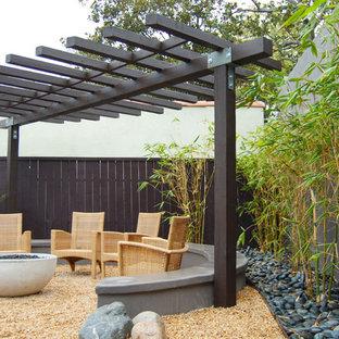 Idee per un patio o portico etnico di medie dimensioni e dietro casa con un focolare e ghiaia