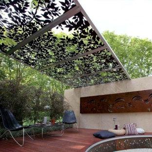 Ispirazione per un grande patio o portico bohémian con pedane e una pergola