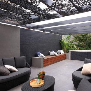 Immagine di un patio o portico minimalista di medie dimensioni e nel cortile laterale con piastrelle e una pergola