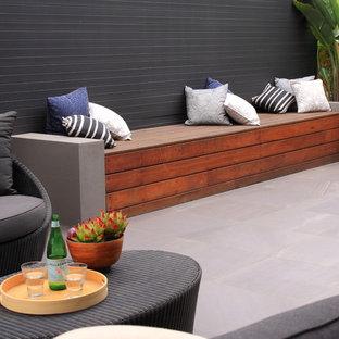 Ispirazione per un patio o portico moderno di medie dimensioni e nel cortile laterale con piastrelle e una pergola