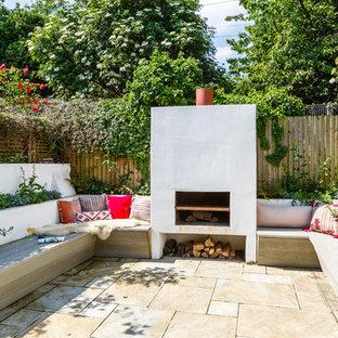 Esempio di un patio o portico eclettico con piastrelle, nessuna copertura e un caminetto