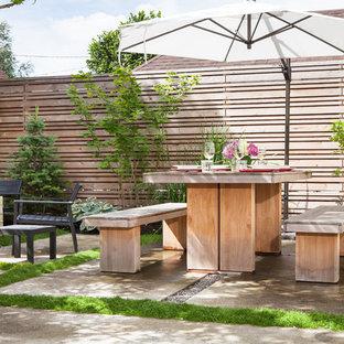 Esempio di un piccolo patio o portico moderno dietro casa con pavimentazioni in cemento e un parasole