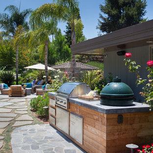Esempio di un ampio patio o portico tradizionale dietro casa con pavimentazioni in pietra naturale e nessuna copertura