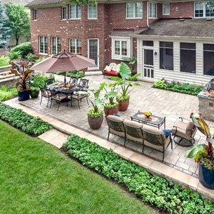 Foto de patio tradicional, grande, sin cubierta, en patio trasero, con brasero y adoquines de ladrillo