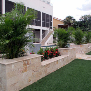 Inspiration for a mid-sized mediterranean backyard stone patio remodel in Tampa