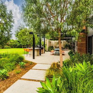 Esempio di un grande patio o portico moderno nel cortile laterale con lastre di cemento e una pergola