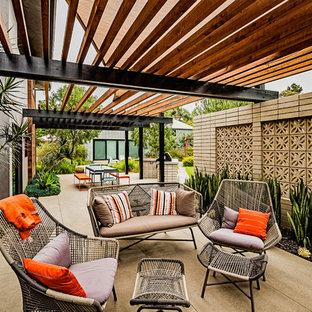 Ejemplo de patio retro, grande, en patio lateral, con losas de hormigón, pérgola y chimenea