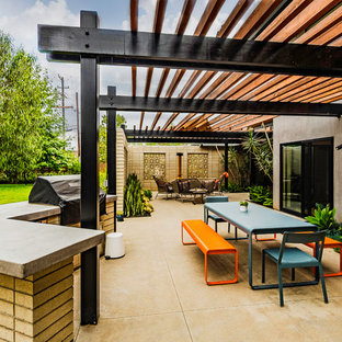 Large 1960s side yard concrete patio photo in San Diego with a fireplace and a pergola