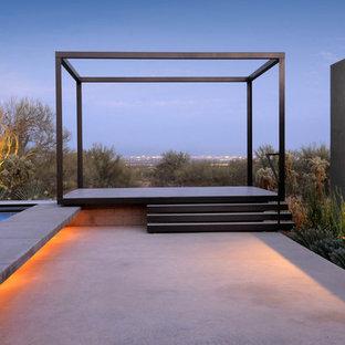 Ispirazione per un patio o portico contemporaneo con lastre di cemento