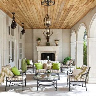 Esempio di un grande patio o portico tradizionale nel cortile laterale con un focolare, un tetto a sbalzo e pavimentazioni in cemento