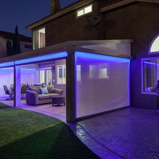 На фото: дворик среднего размера на заднем дворе в средиземноморском стиле с покрытием из бетонных плит и козырьком с