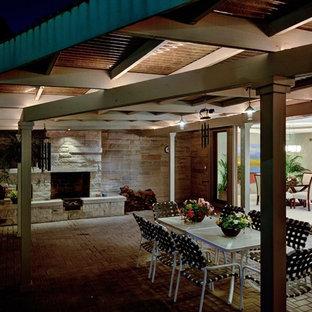 Idee per un patio o portico etnico di medie dimensioni e dietro casa con un focolare, pavimentazioni in mattoni e un tetto a sbalzo