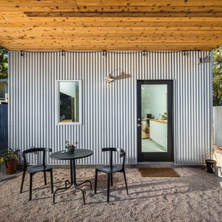 Patio - mid-sized industrial backyard gravel patio idea in Austin with a roof extension