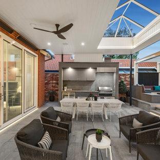 Mid-sized ornate backyard concrete paver patio kitchen photo in Melbourne with a gazebo