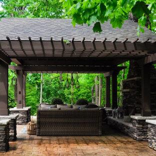 Idee per un grande patio o portico minimal dietro casa con un caminetto, pavimentazioni in cemento e un gazebo o capanno
