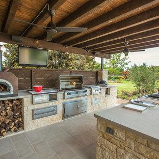 Idee per un grande patio o portico chic dietro casa con pavimentazioni in pietra naturale e un tetto a sbalzo