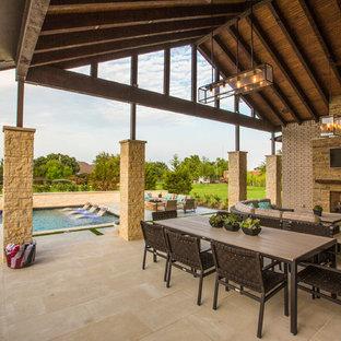 Esempio di un grande patio o portico tradizionale dietro casa con pavimentazioni in pietra naturale, un tetto a sbalzo e un caminetto