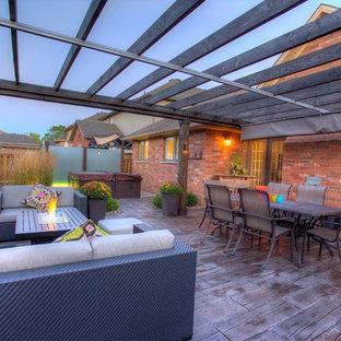 Ispirazione per un grande patio o portico tropicale dietro casa con ghiaia e una pergola