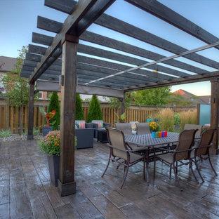Immagine di un grande patio o portico tropicale dietro casa con ghiaia e una pergola