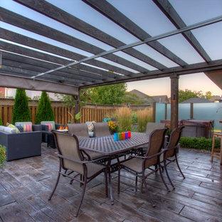 Esempio di un grande patio o portico tropicale dietro casa con ghiaia e una pergola