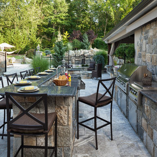 Photo of an expansive mediterranean back patio in New York with an outdoor kitchen, natural stone paving and no cover.
