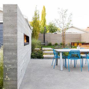 Esempio di un patio o portico design nel cortile laterale con un caminetto, lastre di cemento e nessuna copertura