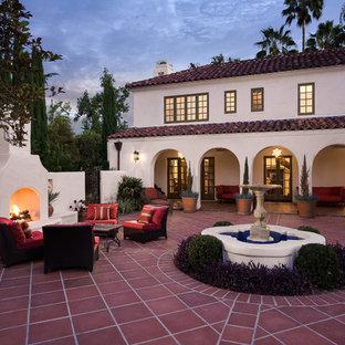 На фото: большой дворик на внутреннем дворе в средиземноморском стиле с покрытием из плитки и уличным камином без защиты от солнца с