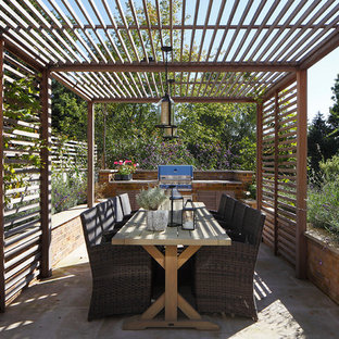 This is an example of a traditional back patio in London with an outdoor kitchen, concrete paving and a pergola.