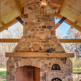 Idee per un patio o portico stile rurale dietro casa con un caminetto e un gazebo o capanno