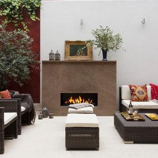 Ispirazione per un patio o portico etnico di medie dimensioni con un focolare e pavimentazioni in pietra naturale