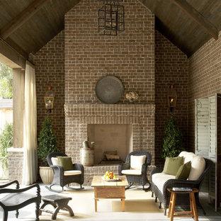 Idée de décoration pour une terrasse tradition avec un foyer extérieur et une extension de toiture.