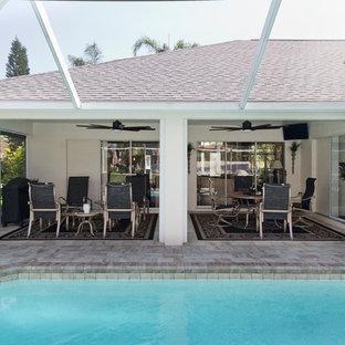 Foto di un grande patio o portico classico dietro casa con piastrelle e un tetto a sbalzo